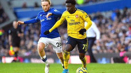 Everton's Tom Davies (left) and Arsenal's Bukayo Saka battle for the ball during the Premier League