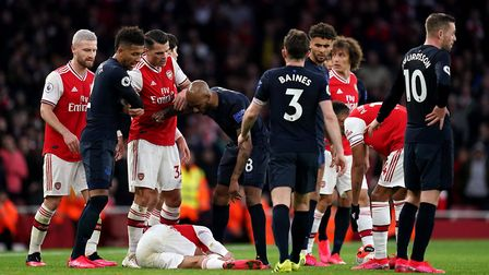 Arsenal's Dani Ceballos lies on the pitch following a foul by Everton's Richarlison (not in picture)