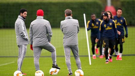 Arsenal manager Mikel Arteta (left) talks to his staff members during the training session at London