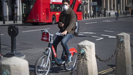 A man wearing a protective face mask cycles in central London, after Prime Minister Boris Johnson ha