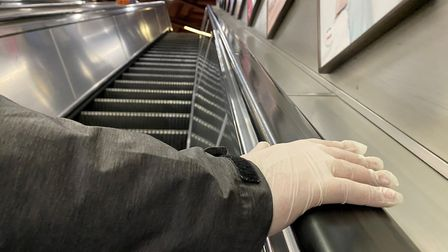 A person with a gloved hand uses an escalator in Baker Street Underground Station in London after Se