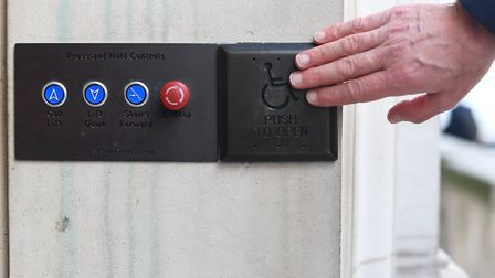A picture posed by a model of a man using a disabled access button with a bare hand in London. Engla