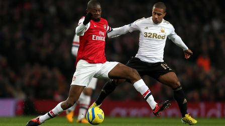 Arsenal's Abou Diaby is challenged by Swansea's Wayne Routledge during the FA Cup Third Round Replay
