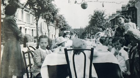 Edna Wilson pictured at a party in her street, Torbay Road, in May 1945. She can be seen peering out