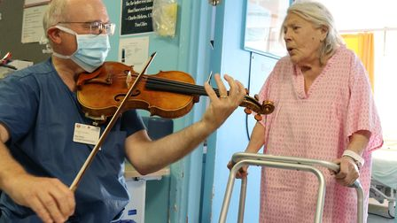 Consultant Maxton Pitcher serenades Northwick Park Hospital patient Jean Pearson. Picture: LNWUH