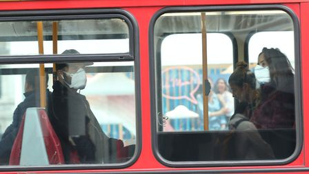 A man and woman wearing protective face masks on a bus in London. Picture: Yui Mok/PA