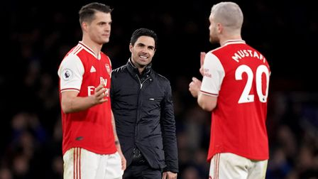 Arsenal's manager Mikel Arteta looks on as Granit Xhaka and Shkodran Mustafi celebrate victory in a