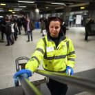 Stock image of staff member wiping down handrails part of enhanced cleaning procedures that Transpor
