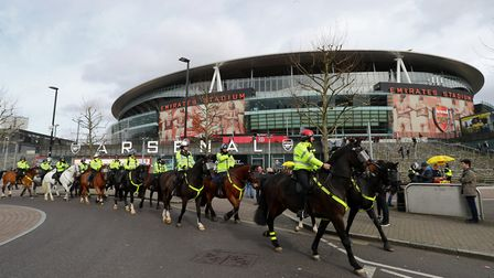 A general view of mounted police riding past the Emirates Stadium