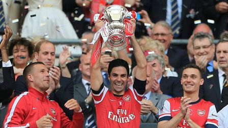 Arsenal head coach Mikel Arteta lifts the FA Cup after the 2014 final against Hull City