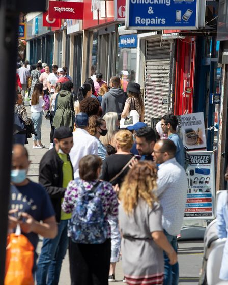 People queue for TK Maxx and Sports Direct in Kilburn High Road as 'non essesntial' shops reopen. Pi