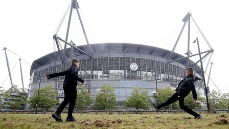 Youngsters play football outside the Etihad Stadium, ahead of the Premier League clash between Manch