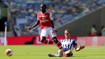 Arsenal's Nicolas Pepe (left) and Brighton's Dan Burn battle for the ball during the Premier League