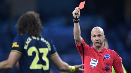 Referee Anthony Taylor shows Arsenal's David Luiz a red card after a challenge on Manchester City's