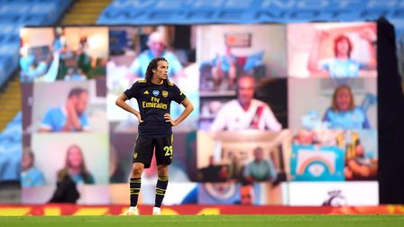 Arsenal's Matteo Guendouzi in front of the giant tv screen which pictures Manchester City fans watch