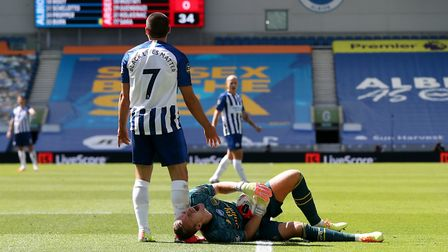 Arsenal goalkeeper Bernd Leno lands awkwardly after a challenge from Brighton's Neal Maupay