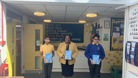 Norma Marshall, head of Earlsmead Primary School with two pupils and their gifted dictionaries. Pict