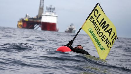"""Greenpeace campaigner Sarah North holds a banner reading """"Climate Emergency"""" whilst floating in fron"""