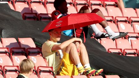 Arsenal's Mesut Ozil shields from the sun under an umbrella in the stands during the Premier League
