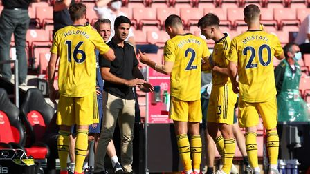 Arsenal manager Mikel Arteta (left) speaks to his team at a drinks break during the Premier League m