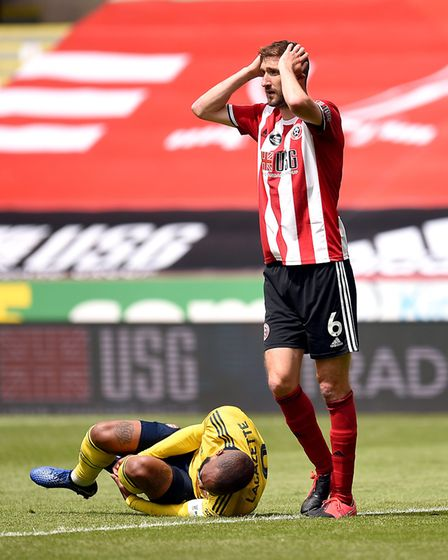 Sheffield United's Chris Basham reacts after he concedes a penalty for a foul on Arsenal's Alexandre