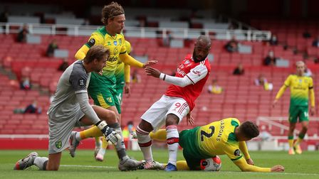Arsenal's Alexandre Lacazette is tackled by Norwich City's Max Aarons (right), with Tom Trybull and