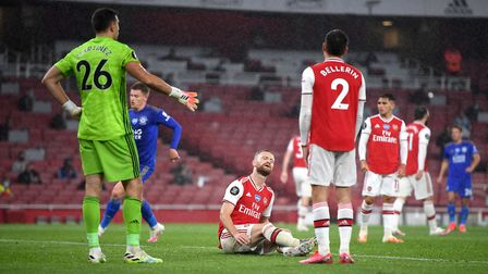 Arsenal's Shkodran Mustafi sits dejected after Leicester's goal
