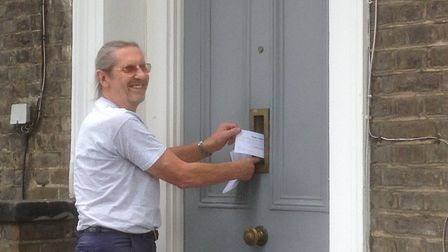 John Hartley delivering the survey leaflets through a letterbox. Picture: Barnsbury and St Mary's Ne