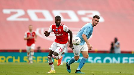 Arsenal's Nicolas Pepe (left) and Manchester City's Aymeric Laporte battle for the ball