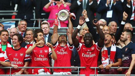 Winning goalscorer Aaron Ramsey of Arsenal (C) lifts the trophy. (Photo by Clive Mason/Getty Images
