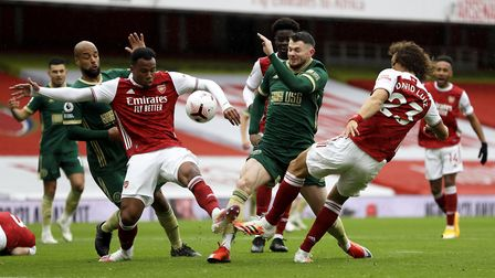 Sheffield United's Oliver Burke (centre) battles for the ball with Arsenal's Gabriel Magalhaes (left