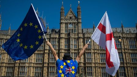 An anti-Brexit demonstrator holding the European Union and England flags outside the Houses of Parli