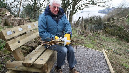 Glebe Field project volunteer David Day holding some of the saplings which have been cut down next t