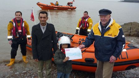 Pappadoms owner Sayd Ahmed and son Samir present the cheque to John Edgerton Preece of the Weston fu