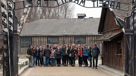 Students enter Auschwitz through the infamous gate, bearing the legend 'arbeit macht frei' - which t