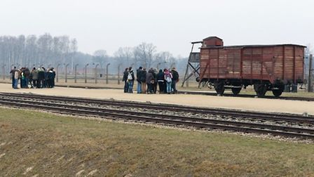 Students study the cattle truck, of the type used to ferry millions to their deaths.