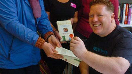 Singe Green signing copies of his book Mums List, to raise money.