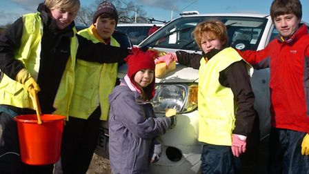 Scouts with buckets and sponges for their car wash.