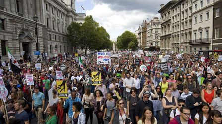 Demonstrators hold placards as they take part in a pro-refugee rally in central London on September