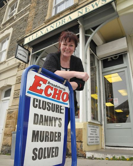 Newsagent Angie Smith with a swingboard advertising for the finale of Broadchurch.