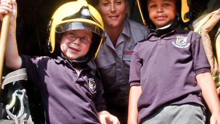 Children being visited by a fire engine.