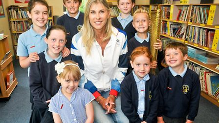 British swimmer Sharron Davies talking to the children and showing them an olympic torch.