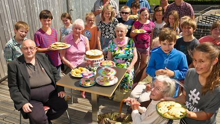 Youngsters serving older residents tea and cakes.