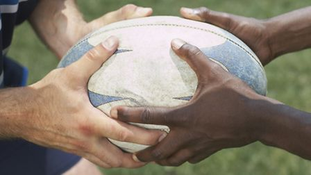 Hands holding rugby ball