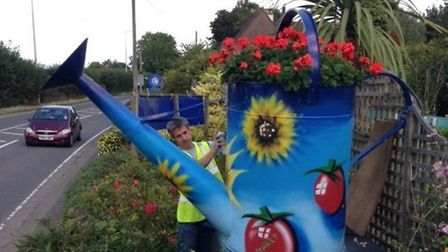 Damien Jeffrey spraying the giant watering can outside Cleeve Nursery