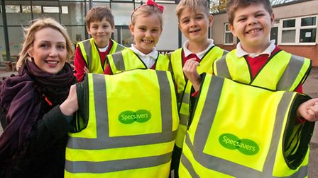 Emma Perrigo from Clevedon's Specsavers handing over high visability jackets to Edward, Katy, Bradle
