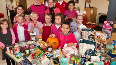 Staff and pupils with harvest gifts for Clevedon Food Bank and dressed in pink to raise money to sup