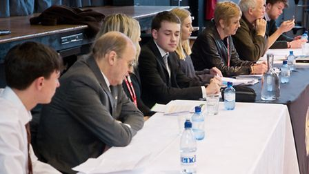 A panel of guests representing local political parties and student speakers before a audience of Six