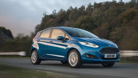 Blue Ford Fiesta on a road