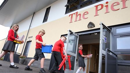 Pupils moving furniture into their new school building.